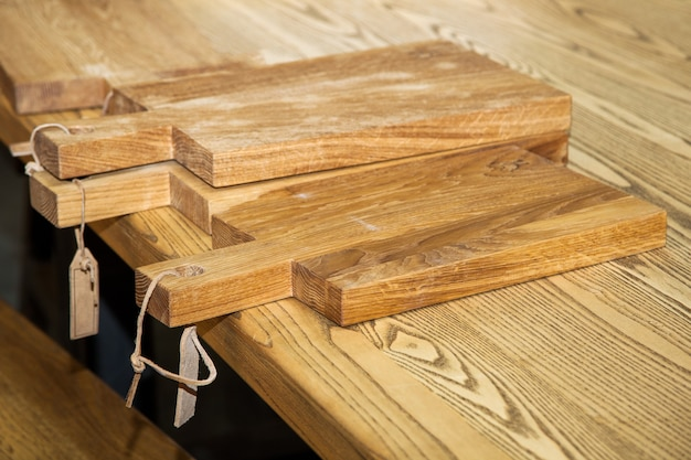 Pile of wooden cutting boards on kitchen table