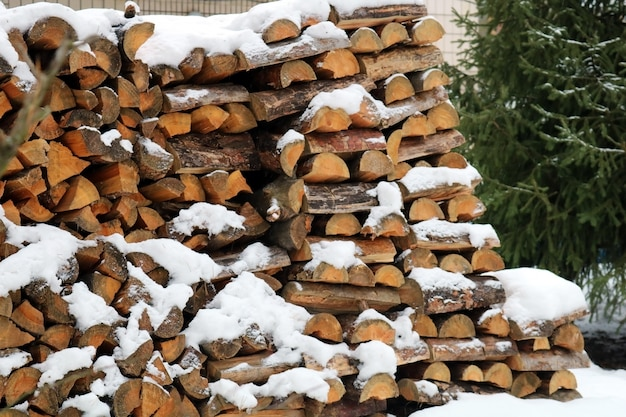 A pile of wooden logs on the background of a winter landscape