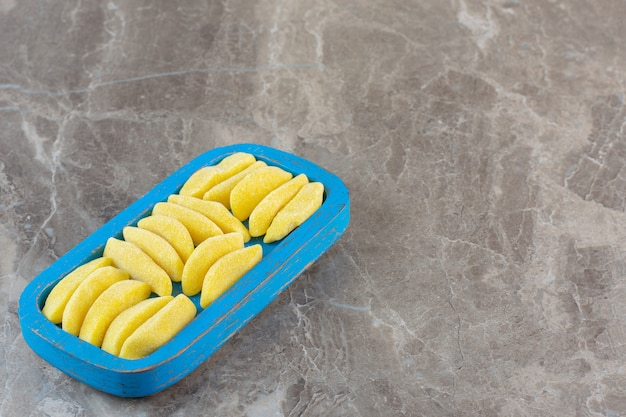 Pile of yellow sweet candies on wooden blue plate.