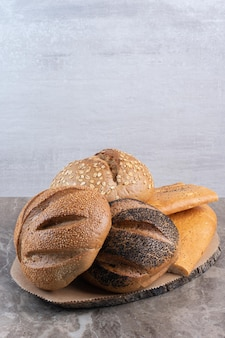Piled assortment of different bread types on marble background. high quality photo