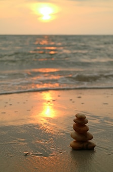 Piled up pebble stones on the sunset beach of thailand