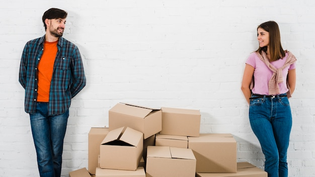 Piles of cardboard boxes between the stylish young couple standing against wall looking to camera