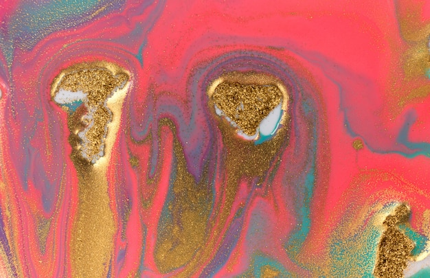 Piles of gold sequins on pink smudges of paint. abstract paint.