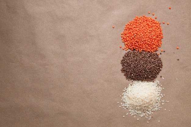 Piles of lentils, buckwheet, rice on the brown background with copyspace