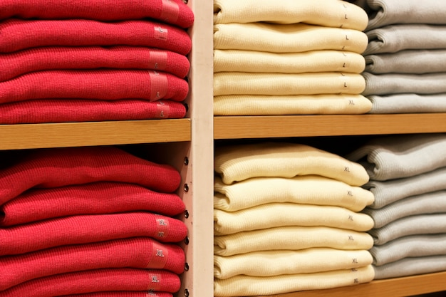 Piles of multicolored clothes on the shelves in store