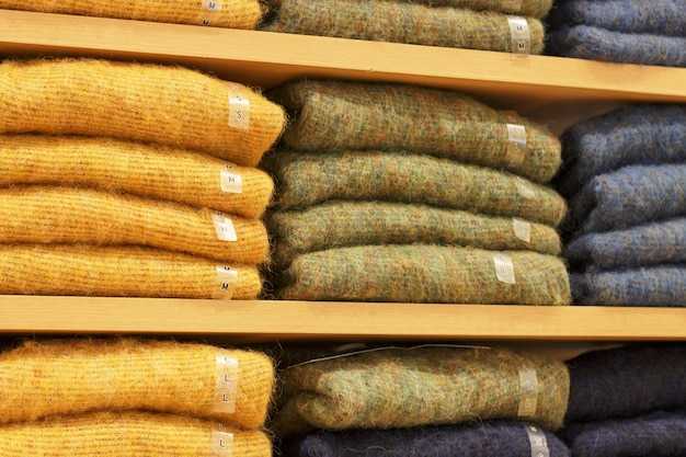 Piles of multicolored sweater on the shelves in store women's clothing