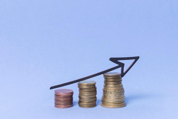 描かれた矢印とコインのお金の山