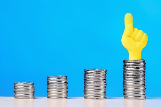 コインの山は人差し指を上にして成長します。投資成長のコンセプト。