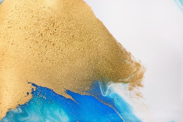 Груды золотых блесток на синих пятнах краски