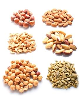 Груды различных орехов и семян, изолированные на белой поверхности. фундук, бразильский орех, миндаль, тыквенные семечки, кешью