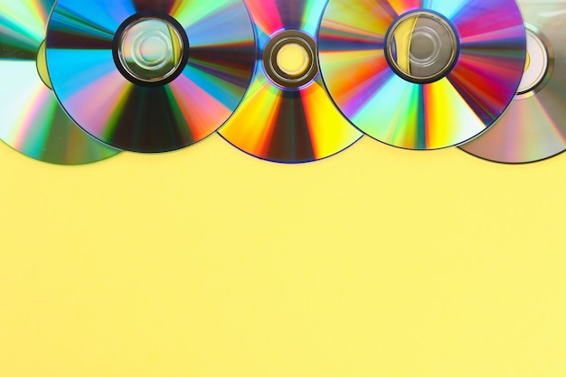 Piles of old  cds,dvd on pastel background. used and dusty disk with copy space for add text.