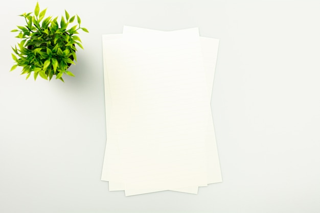 Piles of paper on the white desk background with a copy space - top view.