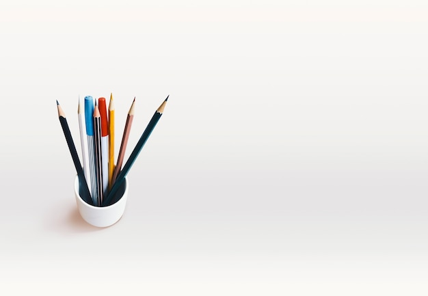 A piles of pencils mixed color and magic pens on white background with copy space.