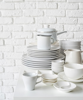 Piles of white ceramic dishes and tableware on the table on white brick wall