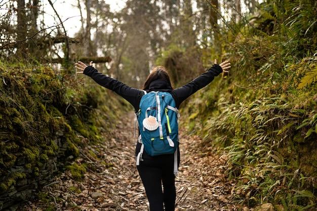 Женщина-пилигрим брюнетка делает поход по камино-де-сантьяго в сент-джеймс