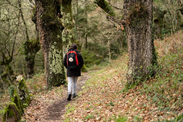 Пилигрим брюнетка женщина с хвостиком черно-красный рюкзак с висящей раковиной делает камино де сантьяго по тропе в окружении деревьев
