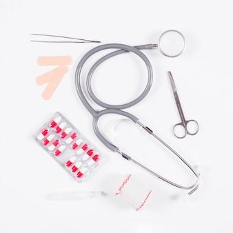 Пакет блистерной упаковки с стетоскопом и медицинским оборудованием на белом фоне Бесплатные Фотографии
