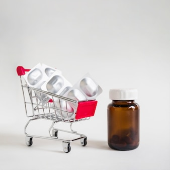 Pill blisters in shopping cart with glass bottle on white background