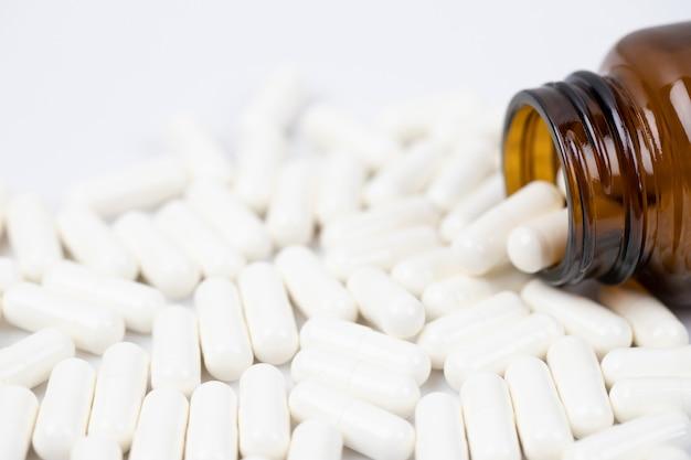 약병이 쏟아져 나옵니다. 흰색 바탕에 표면 정제에 캡슐 알 약. 마약 의료 건강 관리 개념