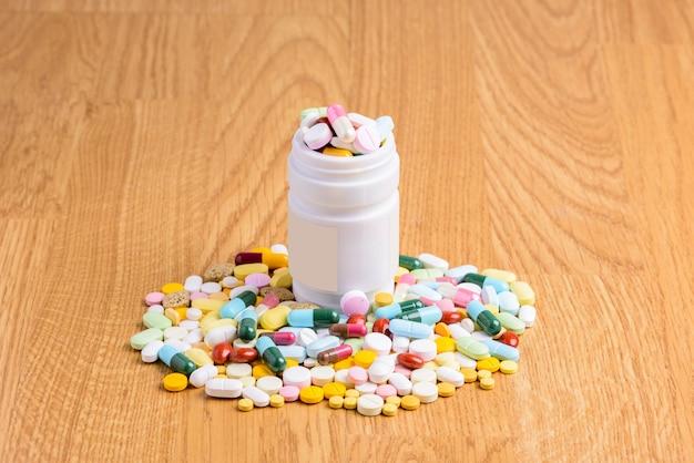 Pill bottle spilling pills on to surface wooden