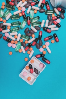 파란색 배경에 여러 가지 빛깔의 알약이 있는 알약 디스펜서