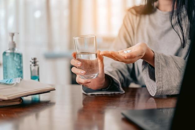 Таблетка в руке молодая женщина держит в руках стакан с водой и таблетки от коронавируса