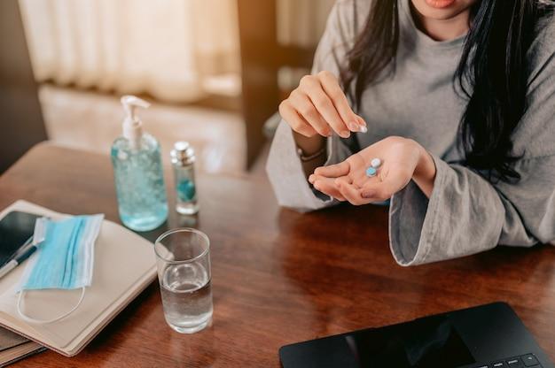 彼女の手に丸薬水と彼女の手に丸薬コロナウイルスとガラスを保持している若い女性