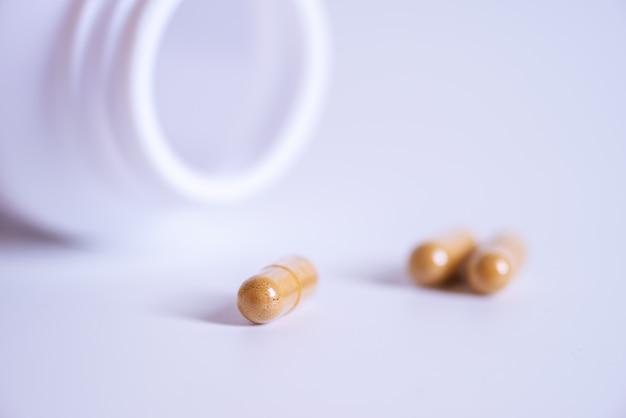 ボトルからこぼれる錠剤のぼやけた背景、健康のための薬のカプセル、ボトルからこぼれるビタミン、マクロ