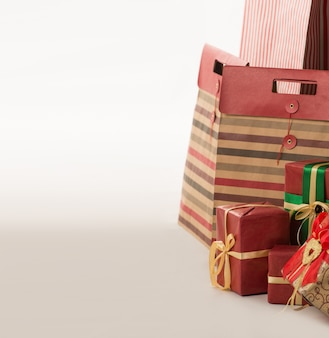 Pillar of boxes with presents wrapped in red paper on white background