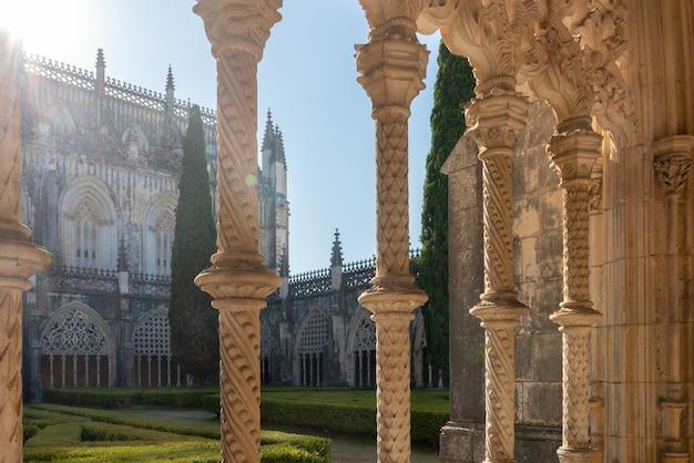 日光が当たるバターリャ修道院の回廊のアーチの柱バターリャポルトガル