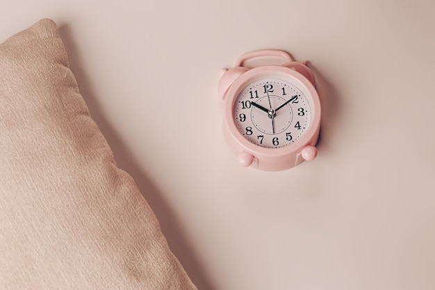 Pillow and alarm clock on a beige background. healthy restful sleep concept.