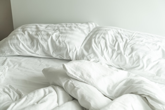 Pillow on bed and with wrinkle messy blanket in bedroom