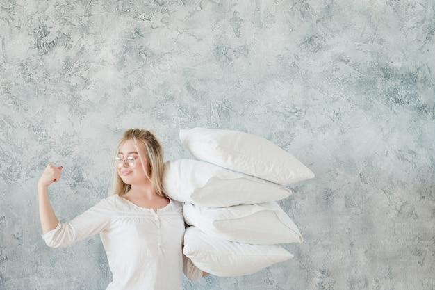 枕の掃除。組織された主婦。枕の山を保持し、上腕二頭筋を示す女性。