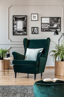 Pillow on emerald green armchair in elegant living room with black and white photos on grey wall