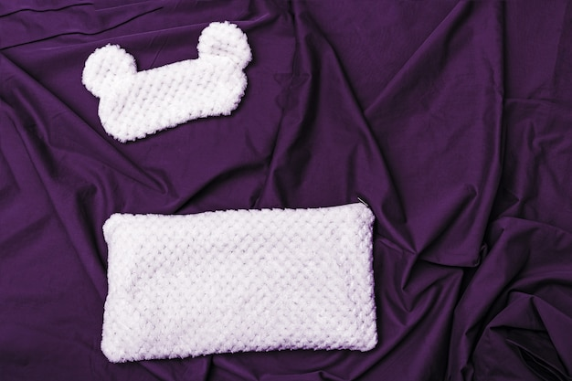 Pillow and eye mask for sleeping from fur on bed with dark puple sheet.