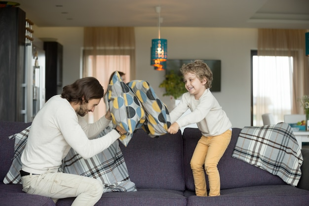 Pillow fight between father and little son in living room