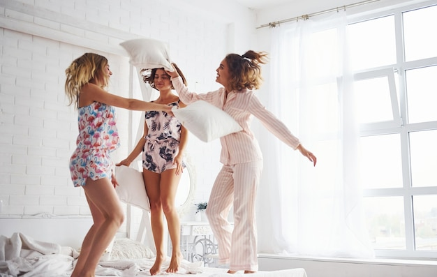枕投げ。寝室でパジャマパーティーで楽しい時間を過ごしている幸せな女性の友人。