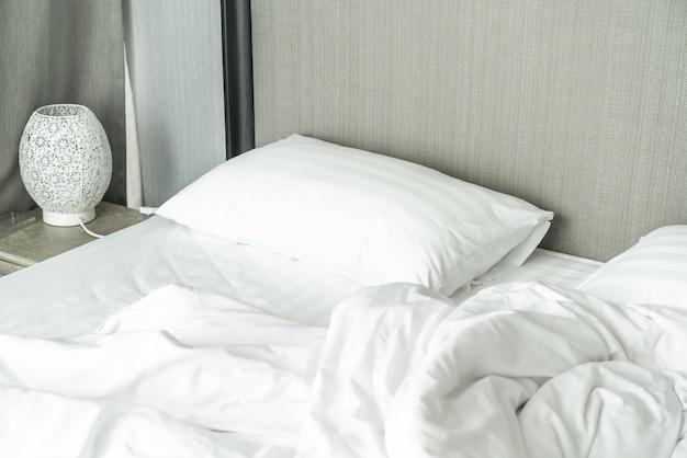 침대와 침실의 주름 지저분한 담요 베개
