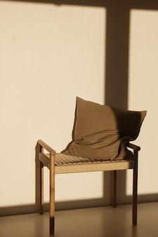 벽에 햇빛 그림자에 고리 버들 세공 벤치에 베개. 최소한의 인테리어 디자인 컨셉