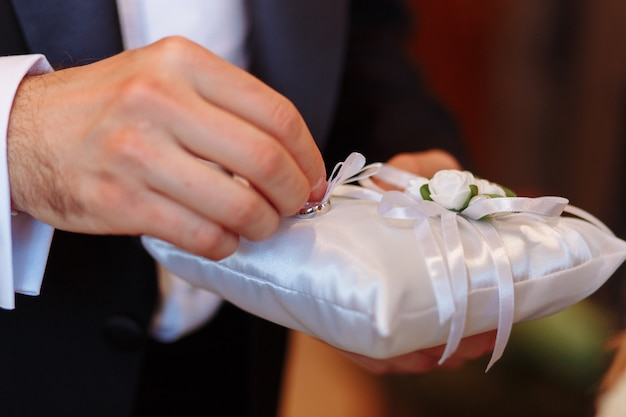 Pillow with wedding rings. groom taking ring during ceremony