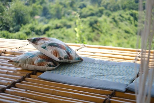 Подушки и одеяла на деревянном столе с видом на зеленые горы на заднем плане.