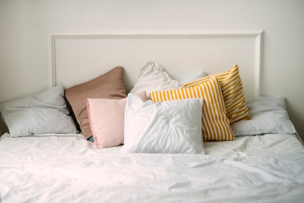 Pillows are lying on the bad near the white wall