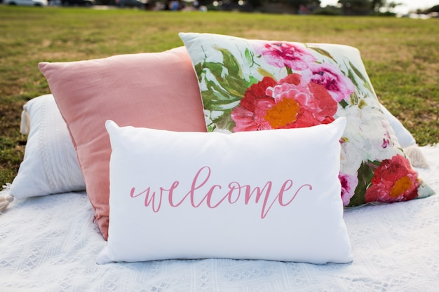 Pillows in the garden with floral print and with a writing