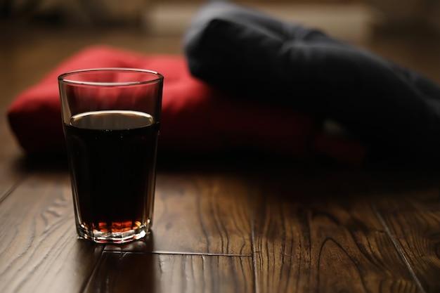 木製の寄木細工の床の枕とガラスのコップの飲み物