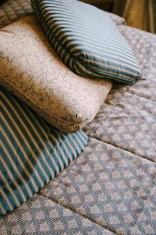 침대 위의 베개 패턴이있는 베개와 줄무늬가있는 두 개의 베개가 오래된 나무 침대에 놓여 있습니다.