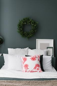 Подушки на кровать с нависшим над ней рождественским венком на темной стене