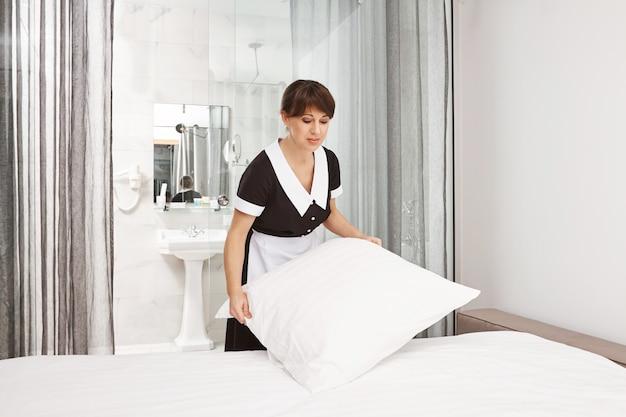 Подушки должны быть белыми, как снег. красивая женщина в униформе горничной заправляет постель, работает уборщицей в отеле или в доме хозяев, сосредоточена на своих обязанностях при уборке спальни