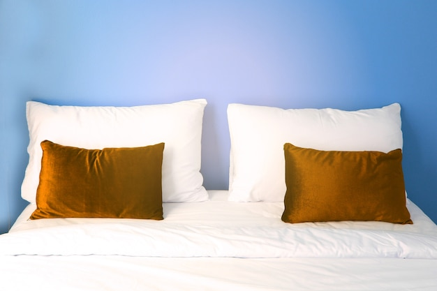 Pillows on the white bed with blue wall in the hotel readying for customer sleeping at nig