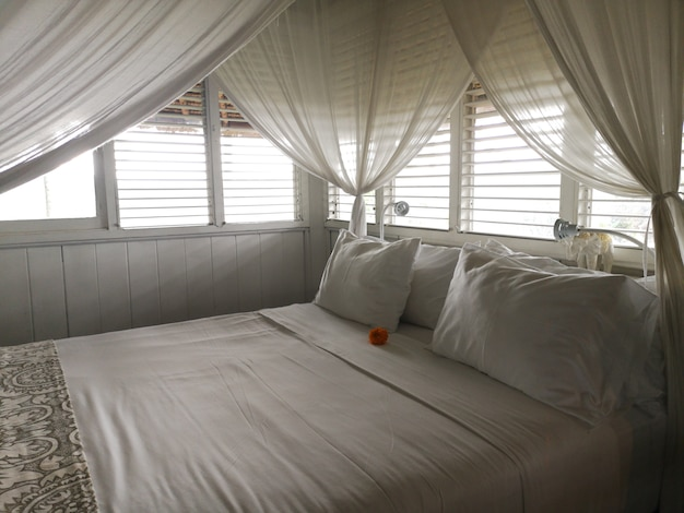 Pillows on a white canopy bed with curtains