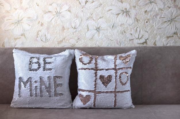 스팽글이 달린 베개. 두 개의 흰색 베개와 쇳조각. 비문이있는 첫 번째 베개는 내 것이라, 두 번째 베개에는 틱택 토가 있습니다. 사랑 개념